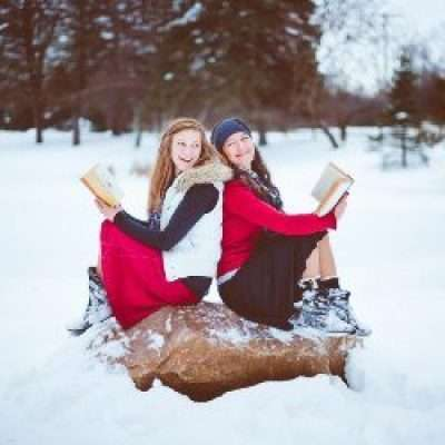 Two women sitting on a rock in the snow holding their Bibles